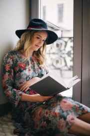 pregnant woman wearing green red and white floral dress reading a book near window