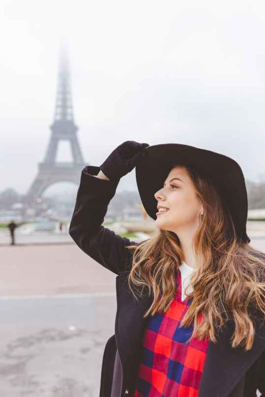 photo of woman standing with eiffel tower in the background