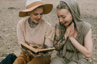 photo of women laughing while reading a book