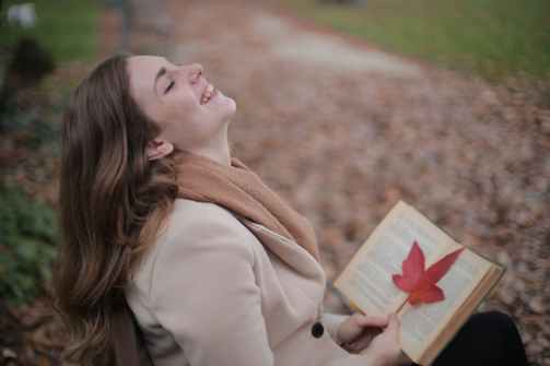 cheerful young woman with red leaf enjoying life and weather while reading book in autumn park